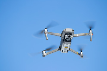 Looking Up at a Quad Copter Drone In Flight against a blue sky Wall mural