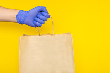 delivery man in medical gloves holding paper craft bag with food containers, supplies from grocery store isolated. safe contactless delivery service, takeout quarantine coronavirus pandemic. mock up Fototapete
