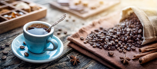Foto op Textielframe koffiebar A cup of aromatic black coffee and coffee beans on the table. Morning Coffee Espresso for breakfast in a beautiful blue cup.
