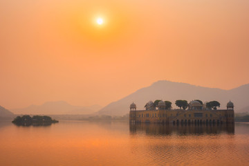 Wall Mural - Tranquil morning at famous indian tourist landmark Jal Mahal (Water Palace) at sunrise in Jaipur. Ducks and birds around enjoy the serene morning. Jaipur, Rajasthan, India