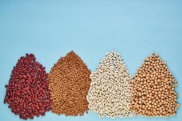 Superfoods and bean seeds, healthy eating concept. Red and white beans, lentils, hummus are scattered on a blue background. Flat lay