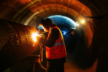 Worker in protective mask welding pipe in tunnel