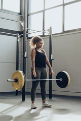 Young woman weightlifting in gym