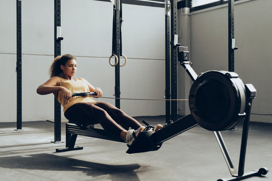 Young woman exercising in gym with rowing machine