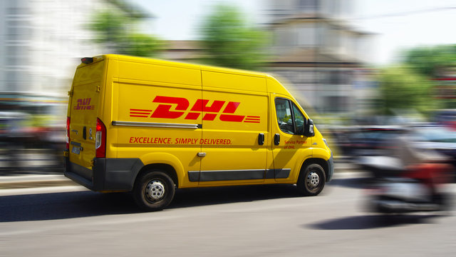 A yellow DHL courier service delivery van