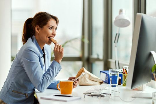 Smiling businesswoman eating a cookie while using mobile phone in the office.