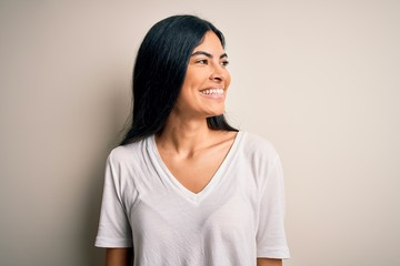 Young beautiful hispanic woman wearing casual white t-shirt over isolated background looking away to side with smile on face, natural expression. Laughing confident.