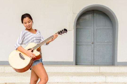 Happy young beautiful Asian woman playing guitar outdoors