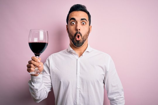 Young handsome man with beard drinking glass of red wine over isolated pink background scared in shock with a surprise face, afraid and excited with fear expression