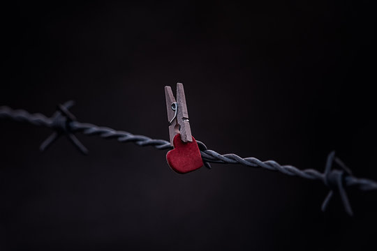 Low Angle View Of Red Heart Shape Decoration With Clothespin Attached To Barbed Wire