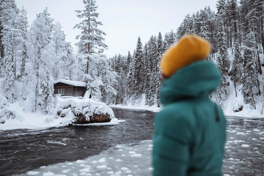 Woman at a frozen river in Lapland, Finland