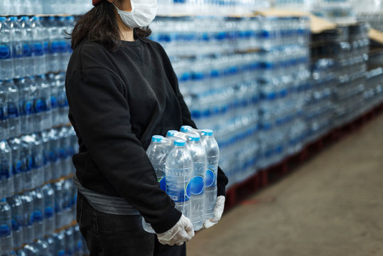 Woman carrying drinking waters with gloved hands during coronavirus pandemic