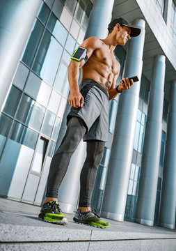 Man looking at his phone while exercising. City workout with smart gadgets and sport applications