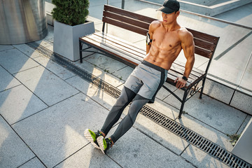 Strong man working out arms muscles doing triceps dips using bench. Photo of man with perfect body outdoor. Strength and motivation