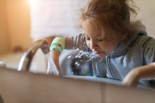 Cute little child girl rinses her mouth with water, looking at mirror and spits water into the sink, at domestic bathroom, side view