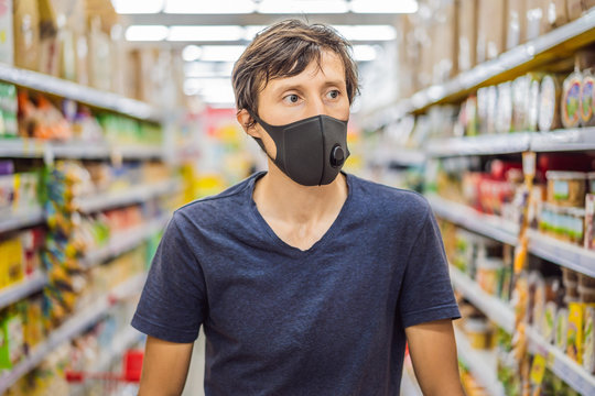 Alarmed man wears medical mask against coronavirus while grocery shopping in supermarket or store- health, safety and pandemic concept - young woman wearing protective mask and stockpiling food