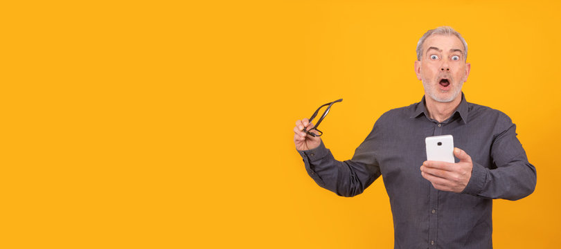 amazed adult or senior man with book isolated on color background
