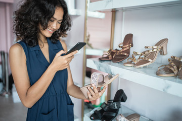 fashion shop owner at his boutique store checking her product and take picture using smart phone