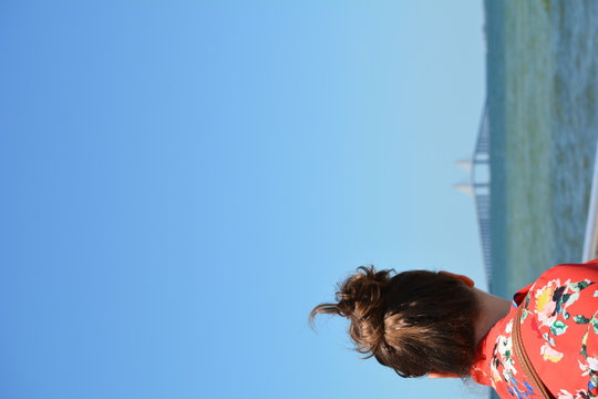 Woman Looking At Sunshine Skyway Bridge Over Tampa Bay Against Clear Blue Sky