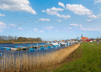 The small boat marina in the village of Schaprode on the German island of Rügen in the Baltic Sea. In the foreground is reed and in the background the small village with a church.