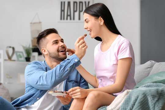 Beautiful young couple eating chocolate at home