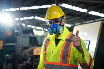 An engineer working in the the industrial. Asian portrait of a young engineer man wear a safety helmet showing thumb up. Yellow hard safety helmet for safety accident and safety goggles mask.
