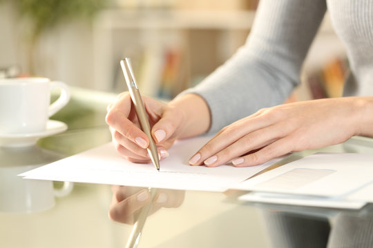 Woman hands writing a letter on a desk at home