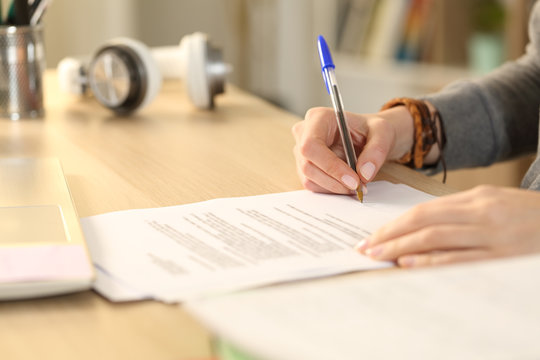 Student girl hands signing contract at home
