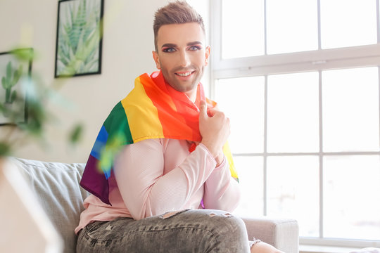 Portrait of young transgender woman with flag of LGBT at home