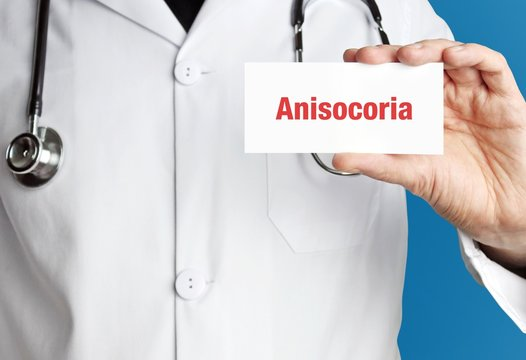 Anisocoria. Doctor in smock holds up business card. The term Anisocoria is in the sign. Symbol of disease, health, medicine