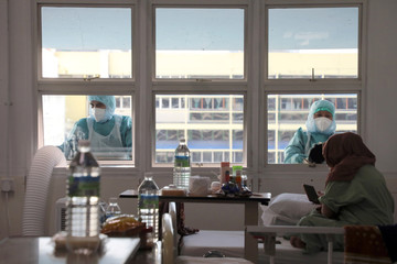 Workers wearing protective suits clean the windows outside the coronavirus disease (COVID-19) ward at Kuala Lumpur Hospital, in Kuala Lumpur
