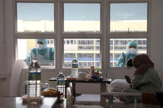 Workers wearing protective suits clean the windows outside the coronavirus disease (COVID-19) ward at Kuala Lumpur Hospital, in Kuala Lumpur