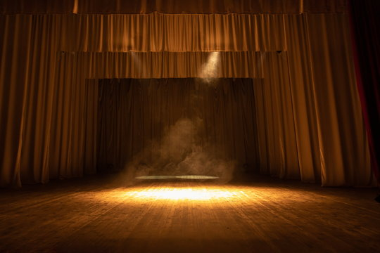 Theater stage with puffs of smoke, illuminated by stage light.