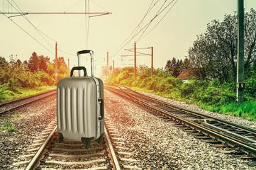 Spoed Fotobehang Spoorlijn Railroad tracks and travel bag close up at sunset