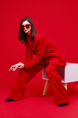 Fashion model in red suit and sunglasses.