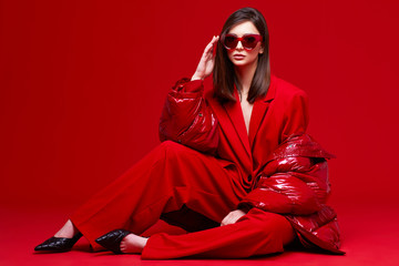 Fashion model in red suit, down jacket and sunglasses.