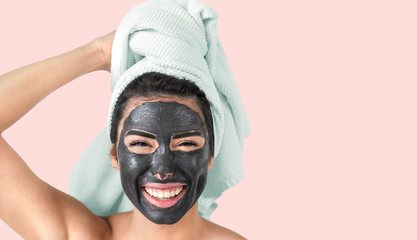 Happy smiling girl applying facial black mask - Young woman having skin care cleanser spa day - Beauty clean treatment and cosmetology products concept - Pink background