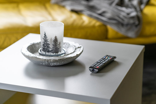 Modern and cozy interior of a living room in a luxury appartement, candle and tv remote on a table with couch in the background