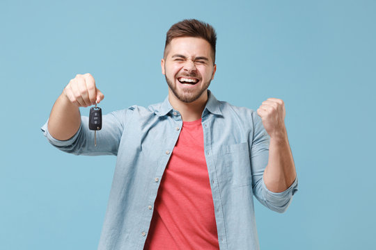 Happy young bearded guy 20s in casual shirt posing isolated on pastel blue wall background studio portrait. People emotions lifestyle concept. Mock up copy space. Hold car keys, doing winner gesture.
