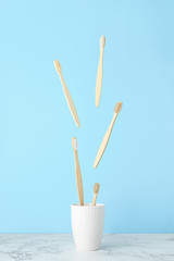 Levitation concept, flying objects. Bamboo toothbrushes fly over a white mug on a light blue background. Zero waste, no plastic. Vertical orientation.