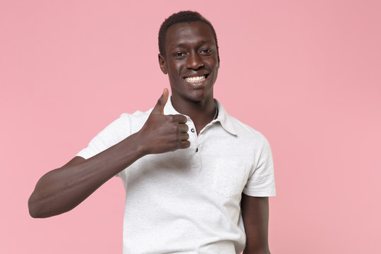 Smiling young african american man guy in white polo shirt posing isolated on pastel pink background studio portrait. People sincere emotions lifestyle concept. Mock up copy space. Showing thumb up.