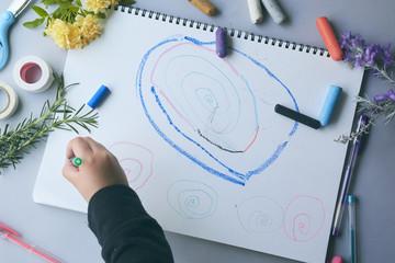画用紙に絵を描くこどもの小さな手