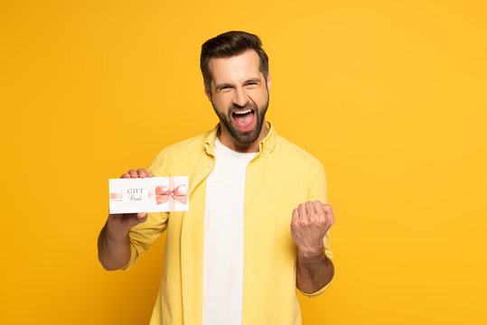Cheerful man showing yeah gesture and holding gift card on yellow background