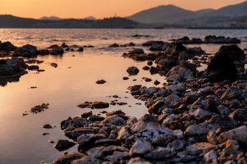 Fototapete - Beautiful bright sunset by the sea overlooking the hills. Rocky seashore. Natural background and texture. Shore of the Mediterranean Sea in Turkey, Bodrum.