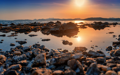 Wall Mural - Beautiful bright sunset by the sea overlooking the hills. Rocky seashore. Natural background and texture. Shore of the Mediterranean Sea in Turkey, Bodrum.