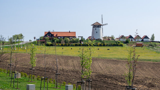 Bukovany, Czech Republic / Southern Moravia - April 18, 2020: Bukovany wind mill and orchard with field