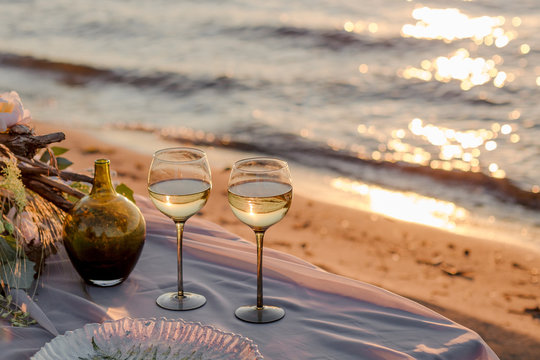 two glasses of champagne and a red rose on the beach