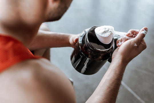 cropped view of sportsman holding jar and measuring spoon with protein powder