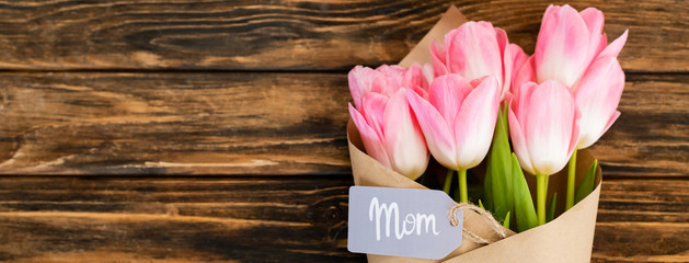 Self adhesive Wall Murals Floral panoramic shot of tag with mom lettering on pink tulips wrapped in paper on wooden surface, mothers day concept