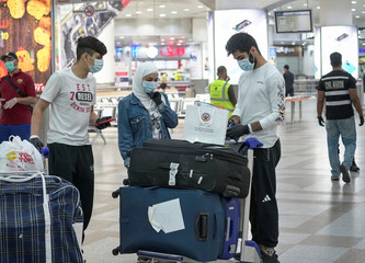 Repatriated Kuwaitis from Amman, wearing protective face masks, following the outbreak of the coronavirus disease (COVID-19), prepare their luggage while arriving at Kuwait Airport